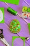 相当与明亮的花卉样式的绿色复活节彩蛋装饰 毛毡蛋装饰,剪刀,纸模板,螺纹,塑料盒 免版税图库摄影
