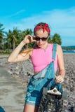 相当与longboard的性感的少妇在晴朗的天气的立场在海前面和棕榈 做活跃体育的女性  免版税库存照片