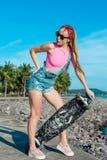 相当与longboard的性感的少妇在晴朗的天气的立场在海前面和棕榈 做活跃体育的女性  免版税库存图片