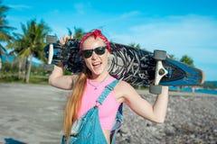 相当与longboard的性感的少妇在晴朗的天气的立场在海前面和棕榈 滑稽的微笑的女性 休闲 库存照片