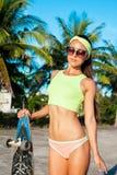 相当与longboard的性感的少妇立场在晴朗的天气的棕榈前面 微笑的女性 休闲 免版税库存照片