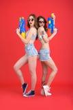 相当两个妇女朋友用水戏弄枪 免版税库存照片