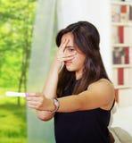相当举行怀孕家庭测试,震惊表情的年轻深色的妇女偷看通过手指,书架 库存照片