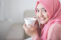 相当亚裔享用咖啡的妇女佩带的hijab 免版税库存照片