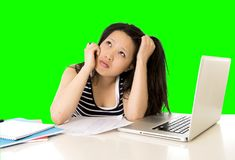 相当亚裔女学生在她的在绿色屏幕croma钥匙的膝上型计算机劳累了过度 免版税库存照片