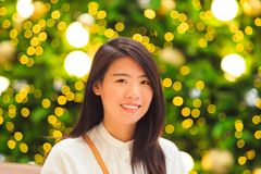 相当亚裔妇女室内画象有圣诞灯背景 图库摄影