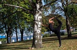 相当亭亭玉立的女孩在公园做瑜伽 站立在平衡的脚在分裂的 免版税库存照片