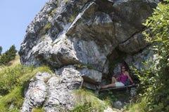 相当休息在岩石风雨棚的女性远足者 免版税库存照片