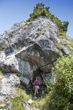 相当休息在岩石风雨棚的女性远足者 库存照片
