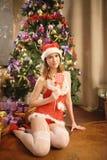 相当佩带圣诞老人的性感的妇女穿衣,坐一个温暖的地毯 库存照片