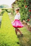 相当使用在一个美丽的庭院里的小女孩 免版税库存照片