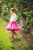 相当使用在一个美丽的庭院里的小女孩 免版税图库摄影
