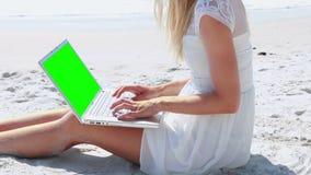 相当使用在海滩的白肤金发的妇女膝上型计算机 影视素材