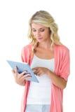 相当使用她的片剂个人计算机的年轻金发碧眼的女人 免版税库存图片