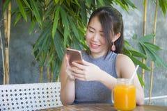 相当使用手机享用的中国亚裔妇女互联网放松送文本社会媒介聊天在咖啡店户外 免版税图库摄影