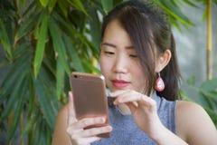 相当使用手机享用的中国亚裔妇女互联网放松送文本社会媒介聊天在咖啡店户外 免版税库存图片