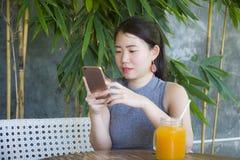 相当使用手机享用的中国亚裔妇女互联网放松送文本社会媒介聊天在咖啡店户外 库存照片