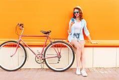 相当使用有减速火箭的自行车的凉快的微笑的少妇智能手机在五颜六色的桔子 图库摄影