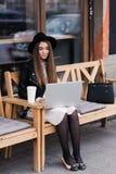 相当使用网书的女性自由职业者为距离工作,当坐长凳户外在咖啡店时 图库摄影