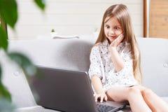 相当使用膝上型计算机的小女孩 免版税库存照片