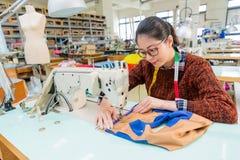 相当使用裁缝机器的女性缝合的工作者 图库摄影