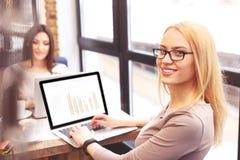 相当使用计算机的两名妇女为工作 免版税库存照片
