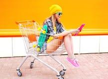 相当使用读书片剂个人计算机的凉快的女孩在购物在五颜六色的桔子的台车推车 库存照片