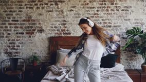 相当便衣的粗心大意的女孩在卧室跳舞并且听到与无线耳机的音乐 年轻 股票视频