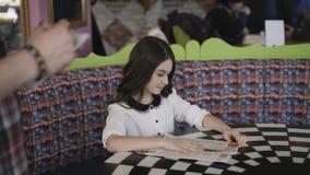 相当做在咖啡馆的年轻和微笑的女孩命令 4K 股票录像