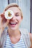 相当做鬼脸用杯形蛋糕的白肤金发的妇女 免版税库存图片