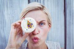 相当做鬼脸用杯形蛋糕的白肤金发的妇女 免版税库存照片