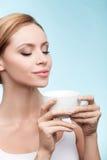 相当健康女孩享用热的茶 免版税图库摄影