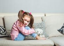 相当偶然佩带的坐沙发有玩具狗的和微笑的愉快的小女孩 免版税库存图片
