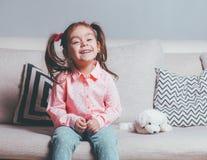 相当偶然佩带的坐沙发有玩具狗的和微笑的愉快的小女孩 库存照片