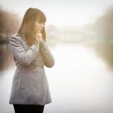 相当冷气候的哀伤的女孩在雾的河附近 免版税图库摄影