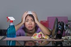 相当劳累过度的年轻人和工作国内清洁和洗涤物与浪花瓶的被注重的亚裔韩国服务佣人妇女恼怒 库存图片