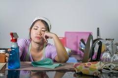 相当劳累过度的年轻人和工作国内清洁和洗涤物家庭厨房stresse的沮丧的亚裔中国服务佣人妇女 库存图片