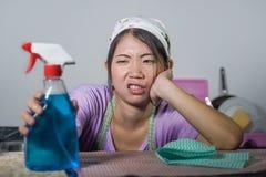 相当劳累过度的年轻人和工作国内清洁和洗涤物家庭厨房stresse的沮丧的亚裔中国服务佣人妇女 免版税库存图片