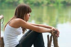 相当十几岁的女孩坐码头 免版税图库摄影