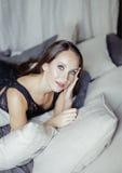 相当卧室内部微笑的年轻深色的妇女 免版税图库摄影