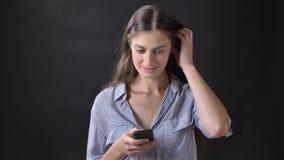 相当发短信在电话和微笑的镶边衬衣的少妇,站立隔绝在黑背景 股票录像