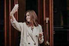 相当可爱的妇女做与巧妙的电话的selfie,穿戴在雨衣,室外的姿势,用途现代技术,份额照片  免版税库存图片