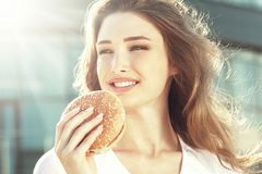 相当吃在城市晴朗的街道上的少妇汉堡包 免版税库存照片