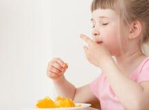 相当吃桔子的小女孩 免版税图库摄影