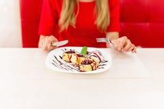 相当吃点心的白肤金发的少妇在餐馆 免版税图库摄影