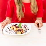 相当吃点心的白肤金发的少妇在餐馆 免版税库存照片