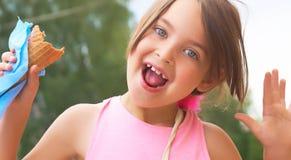 相当吃的小女孩舔在奶蛋烘饼锥体愉快笑的大冰淇凌在自然背景 图库摄影