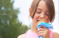 相当吃的小女孩舔在奶蛋烘饼锥体愉快笑的大冰淇凌在自然背景 库存照片