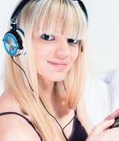 相当听到在她的smartphone的音乐的白肤金发的女孩 库存图片