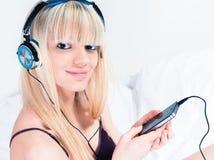 相当听到在她的smartphone的音乐的白肤金发的女孩 库存照片